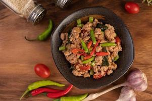 salade de porc hachée épicée avec riz, chili et tomates sur une assiette noire photo