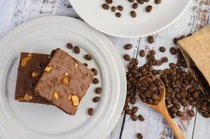 Brownies au chocolat sur une plaque blanche et grains de café sur une cuillère en bois