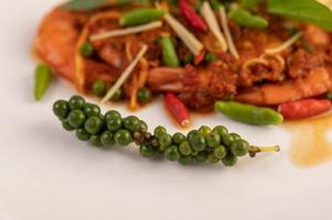 Crevettes chu-chi sur une assiette avec des graines de poivre frais photo