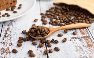 Grains de café dans une cuillère en bois et des sacs de chanvre sur une table en bois blanc