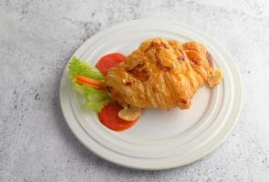 un croissant avec hot-dog sur plat blanc photo