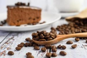Grains de café dans une cuillère en bois sur une table en bois blanc