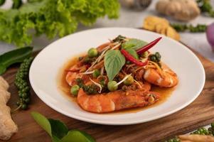 Crevettes chu-chi sur une assiette avec des graines de poivre frais