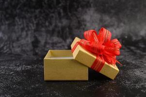boîte-cadeau avec un nœud rouge attaché et ouvert photo