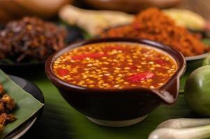 sauce chili et ingrédients sur feuilles de bananier