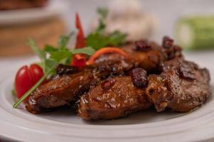 Ailes de poulet frit à la pâte de piment sur un plateau blanc avec du piment et de la coriandre photo