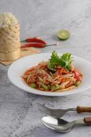 Salade de papaye thaï sur une assiette blanche avec riz gluant, piment, cuillère et fourchette
