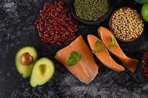 Légumineuses, fruits et saumon sur fond de ciment noir photo