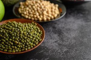 Haricots mungo, haricots rouges et soja sur un fond de sol en ciment noir