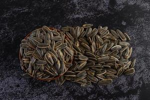 graines de tournesol dans un bol en bois sur une surface noire