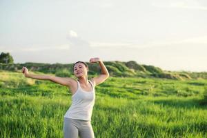Heureuse belle femme aux bras tendus dans un pré photo