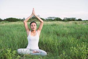 jeune femme, dans, pose yoga, pratiquer, méditation, dans, les, prés photo
