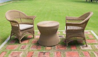 Chaises longues en osier et table avec de l'herbe verte