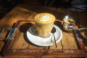 Café avec art latte sur plaque blanche et plateau en bois au soleil photo