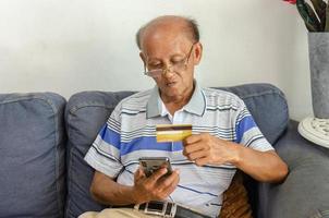 vieil homme utilisant une carte de crédit pour acheter quelque chose en ligne photo