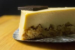 Gros plan d'une tranche de gâteau au fromage sur table en bois et fond sombre photo