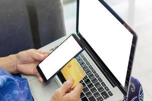 femme tenant un téléphone portable vierge et un ordinateur portable photo