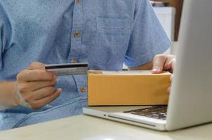 homme tenant une carte de crédit et une boîte en carton