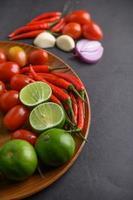 tranches de citron vert, échalotes, ail, tomates, laitue et poivrons sur une assiette en bois