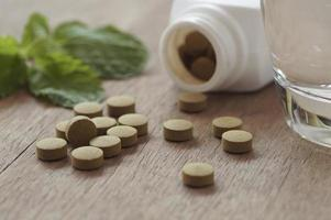pilules brunes avec un verre d'eau