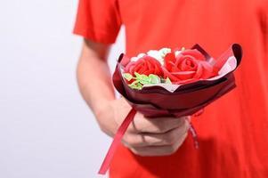 personne tenant un bouquet avec une chemise rouge