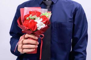 homme portant un costume tenant des fleurs