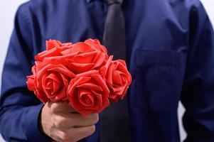 homme en costume bleu tenant des fleurs rouges