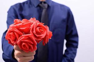 homme en chemise bleue tenant des fleurs rouges