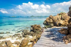 Pont de roche et de bois de l'île tropicale sur la plage avec ciel bleu nuageux