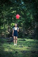 jeune fille tenant des ballons colorés dans la nature