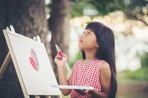 petite fille artiste peignant une image dans le parc photo