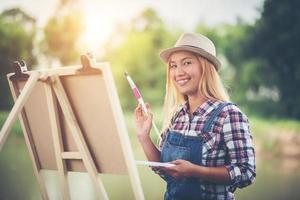 jeune femme dessine une image dans le parc photo