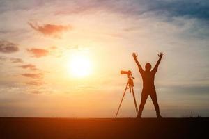silhouette d'un photographe tirant au coucher du soleil photo