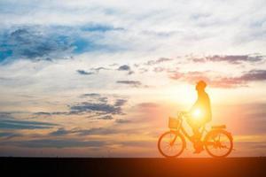 jeune homme fait du vélo sur fond de coucher de soleil photo