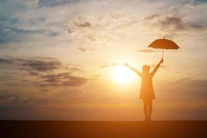 silhouette d'une femme tenant un parapluie sur la plage et le coucher du soleil