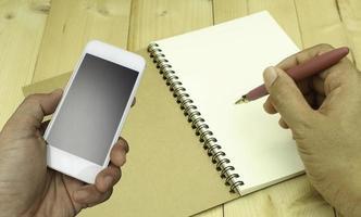 personne utilisant le téléphone et écrivant dans un cahier