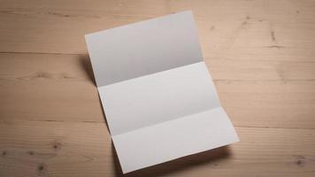 Papier plié blanc blanc sur table en bois