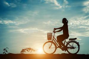 silhouette d'une femme avec un vélo et beau ciel photo
