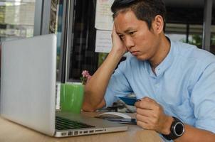 homme tenant une carte de crédit et regardant un ordinateur portable photo
