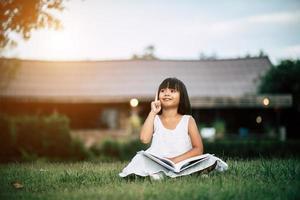 Petite fille lisant un livre dans son jardin à l'extérieur photo
