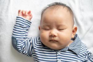 un petit garçon dans une chemise rayée dormant dans son lit photo