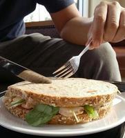 personne se prépare à couper un sandwich