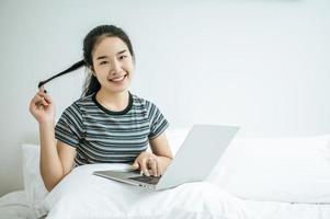 une jeune femme jouant sur son ordinateur portable au lit photo