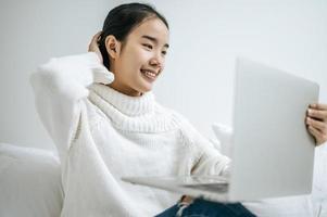 jeune femme portant une chemise blanche jouant sur son ordinateur portable photo