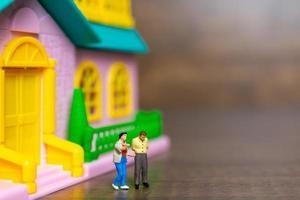deux figurines miniatures devant une maison rose