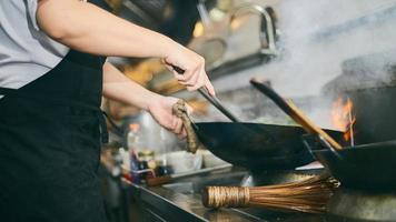 cuisinier travaillant avec wok photo