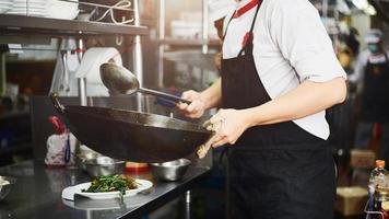 chef jetant de la nourriture dans un wok photo