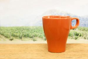tasse orange devant un champ photo