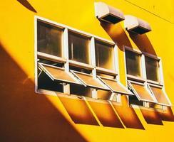mur jaune avec fenêtres en verre