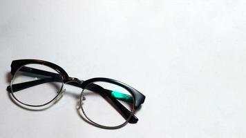 lunettes pliées sur fond blanc photo